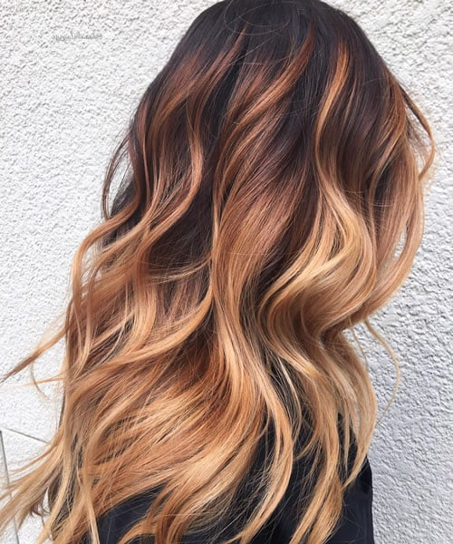 blonde waves with burgundy and strawberry balayage
